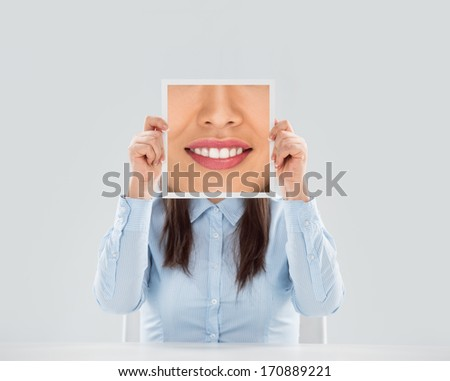 Young woman holding a picture of a smiling mouth in front of her face - stock photo