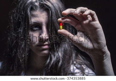Young woman holding a pill addict. Focus on hands - stock photo