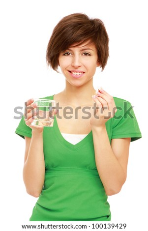 Young woman holding a pill and water, isolated on white - stock photo