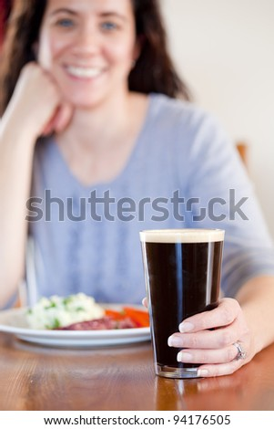 Young woman holding a pint with lunch at a pub