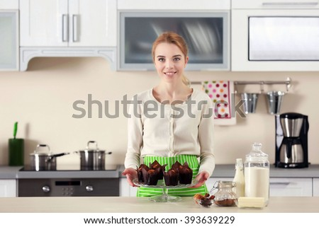 Young woman holding a plate with fresh baked cupcakes
