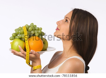 Young woman holding a plate with fresh fruit and tape measure - stock photo