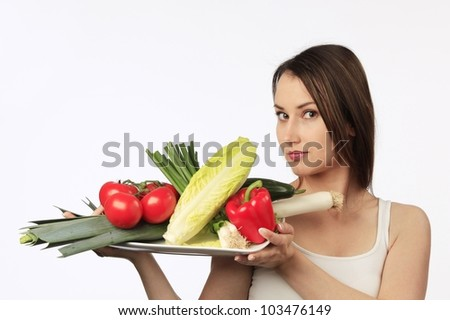 Young woman holding a plate with fresh vegetables - stock photo