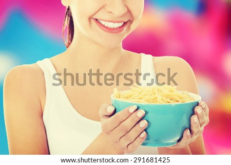 Young woman holding a plate with pasta - stock photo