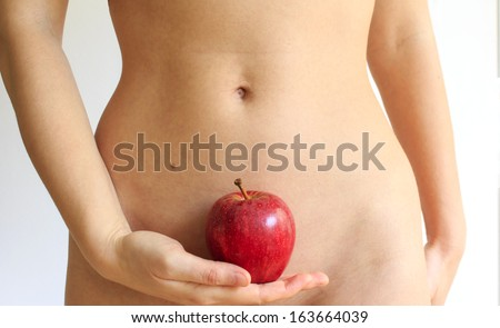 Young woman holding a red apple against her flat stomach. Concept of a good physical shape in a connection to a healthy nutrition / Adam and Eve story - stock photo