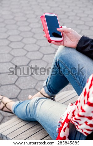 Young woman holding a red covered smartphone. Sitting on a bench, wearing modern shoes, blue jeans, black jacket and a red white scarf. Fashion, technology, life style, online shopping, urban concept. - stock photo