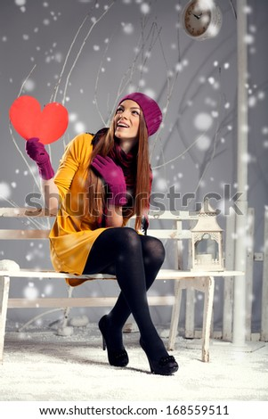 Young woman holding a red heart while sitting on a bench in winter studio interior - stock photo
