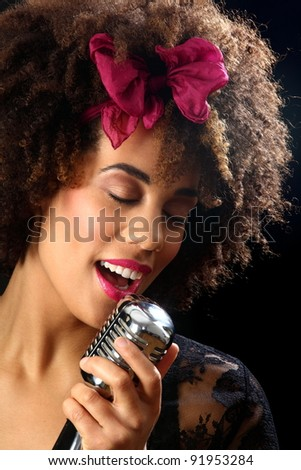 young woman holding a retro microphone and singing - stock photo