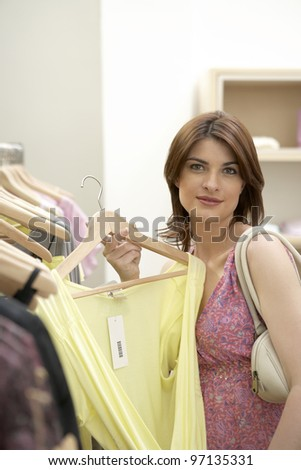 Young woman holding a shirt in a fashion store.