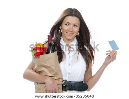 Young woman holding a shopping bag full of groceries and credit card in hands and smiling on a white background - stock photo