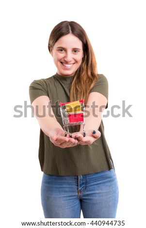 Young woman holding a small cart full of gifts - E-commerce concept - stock photo