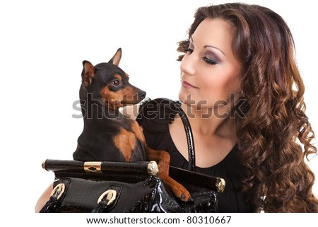 young woman holding a small dog, he is dressed in a black  dress, isolated on white background - stock photo