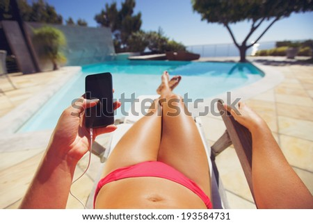 Young woman holding a smart phone by the pool. Female model relaxing on a deckchair using mobile phone. - stock photo