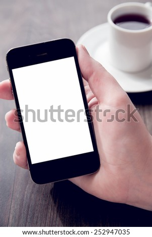 Young woman holding a smartphone with a white screen. Technology, finance, business, baking, online shopping and education concept. Natural window light. - stock photo