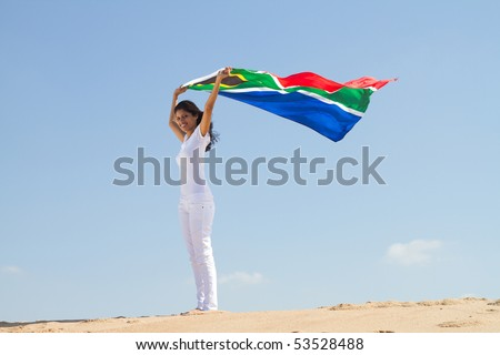 young woman holding a south Africa flag on beach - stock photo