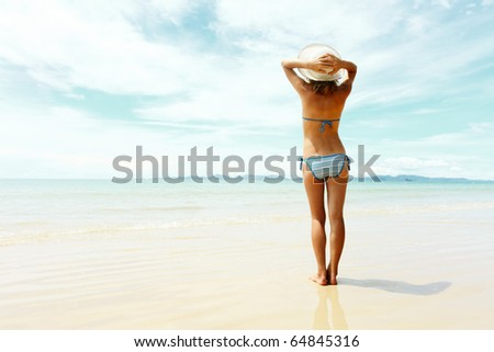 Young woman holding a straw hat and looking to a sea - stock photo
