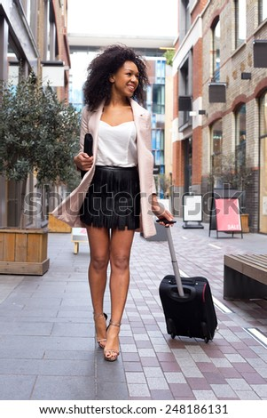 young woman holding a suitcase - stock photo