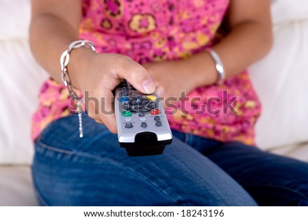 young woman holding a television remote control - stock photo