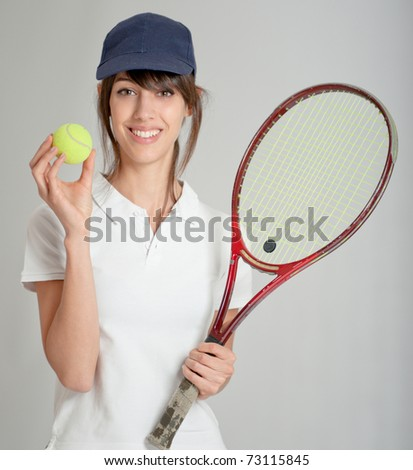 Young woman holding a tennis racket and ball - stock photo