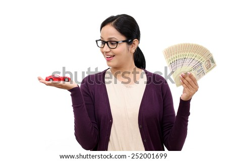 Young woman holding a toy car and Indian rupee notes - stock photo