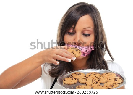 Young woman holding a tray with homemade chocolate cookies and tied mouth with measuring tape, looking at them - stock photo