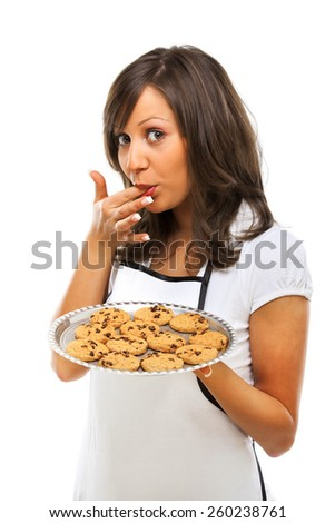 Young woman holding a tray with homemade chocolate cookies, licking her finger and looking at camera - stock photo
