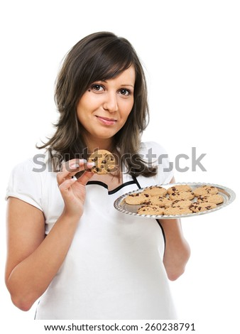 Young woman holding a tray with homemade chocolate cookies, looking at camera - stock photo