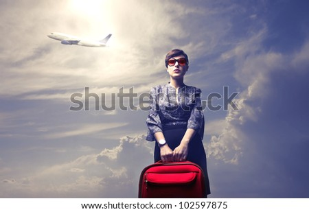 Young woman holding a trolley case with airplane in the background - stock photo