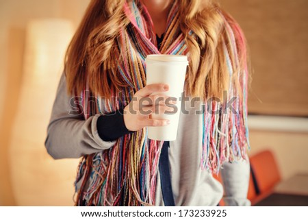 Young woman holding a tumbler of coffee in cafe.