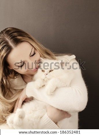 Young woman holding a white fluffy Persian cat - stock photo