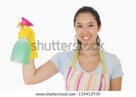 Young woman holding a window cleaner and smiling in apron and rubber gloves - stock photo