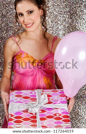Young woman holding a wrapped gift and a pink balloon against a silver glitter background at a birthday party, smiling. - stock photo
