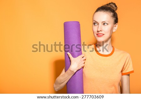 Young woman holding a yoga mat. Fashion, sport and healthy lifestyle concept - stock photo