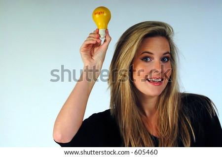 Young woman holding aloft a lightbulb. - stock photo