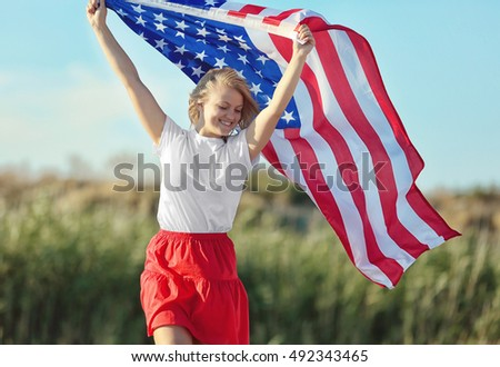 Young woman holding American flag on blue sky background