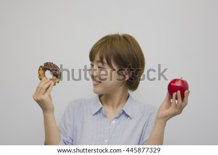 Young woman holding an apple and a doughnut
