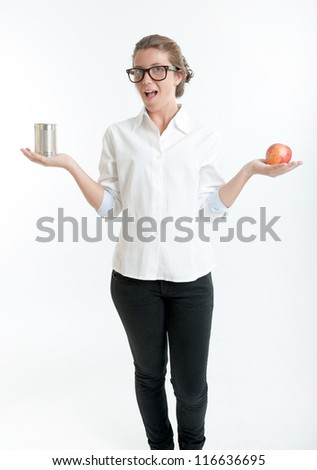 Young woman holding an apple in one hand and a tin in another