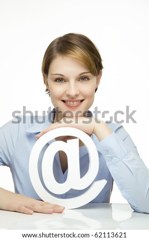 young woman holding an at symbol in her hands - stock photo