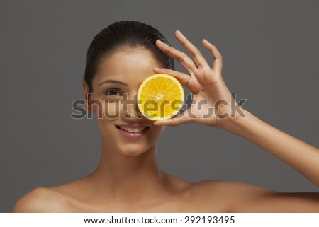 Young woman holding an orange slice over her eye - stock photo