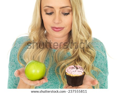 Young Woman Holding and Comparing Cake and Fruit - stock photo