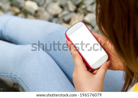 Young woman holding and looking smart phone with blank white empty screen on blurry stone background. - stock photo