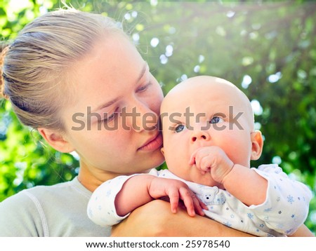 Young woman holding baby girl in a summer garden