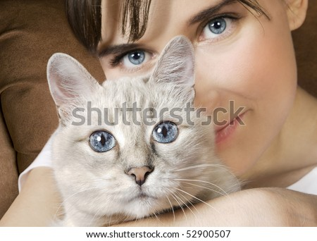 Young woman holding beautiful adult thai cat - stock photo