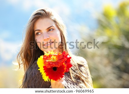 Young woman holding beautiful flowers, enjoying a sunny day outdoor. - stock photo