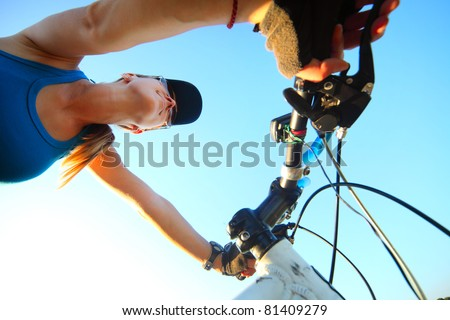 Young woman holding bicycle's handlebar and looking to somewhere. Focus on the face - stock photo