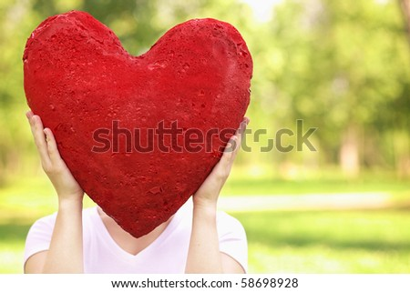 young woman holding big red heart in front of her face - stock photo