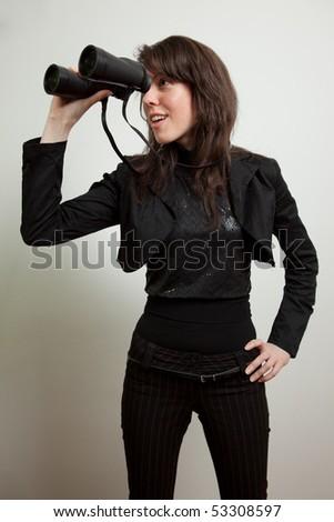 Young woman holding binoculars - stock photo