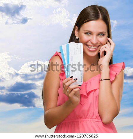Young Woman Holding Boarding Pass against a cloudy sky background - stock photo