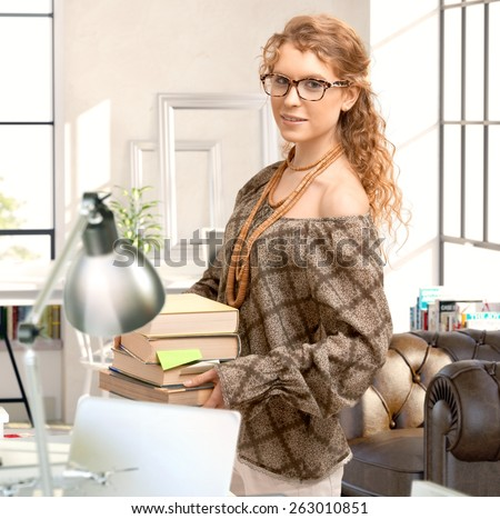 Young woman holding books, looking at camera, smiling. - stock photo