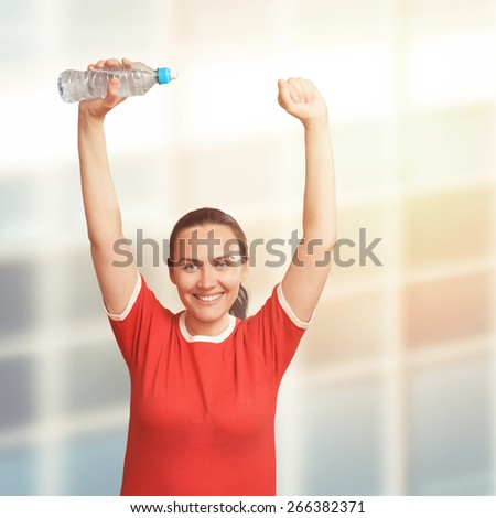 Young  woman holding bottle in hand over her head - stock photo